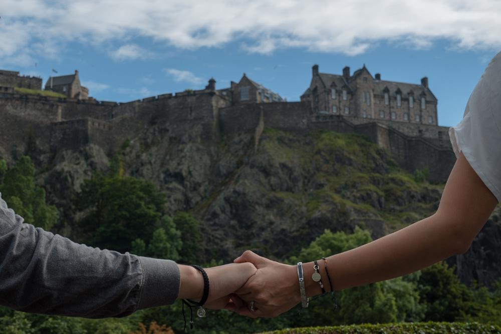 Couple holding hands by Edinburgh Castle