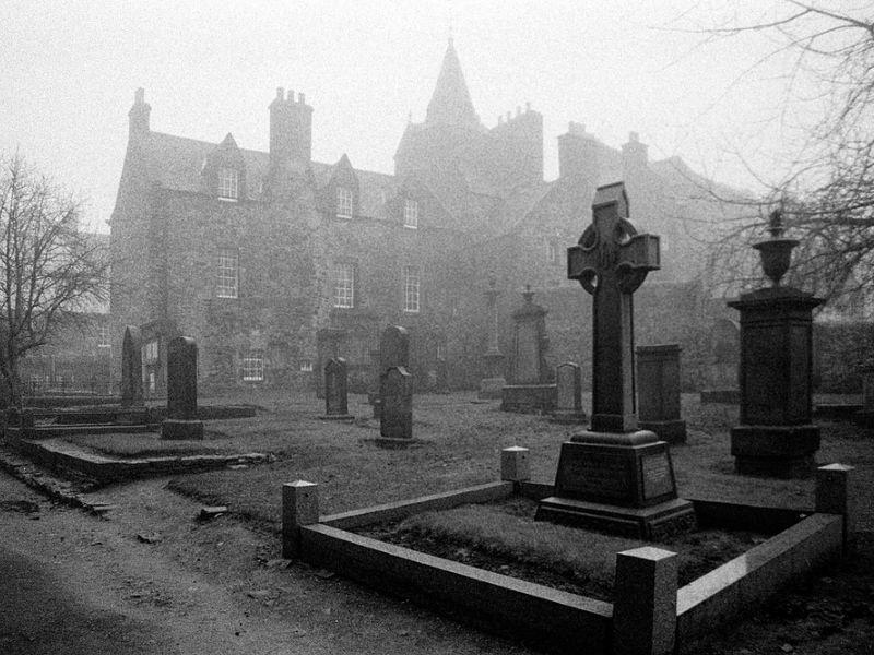 Spooky graveyard in mist