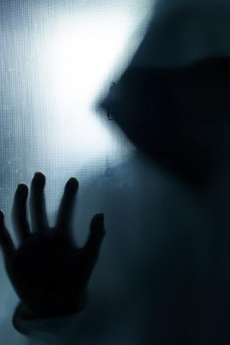 Spooky figure pressing against window