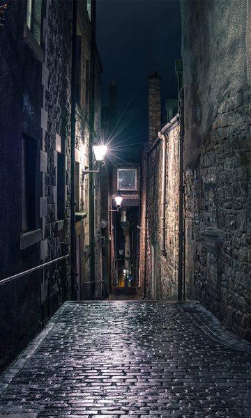 A dark cobbled street in Edinburgh at night lit by an old lamp