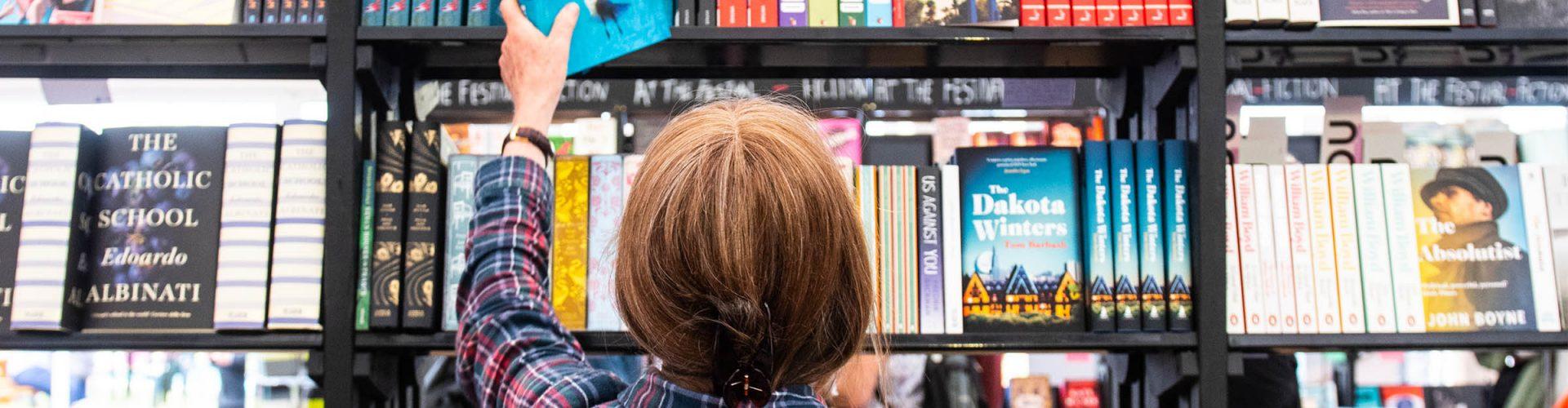A woman choosing a book off the shelf at the Edinburgh International Book Festival