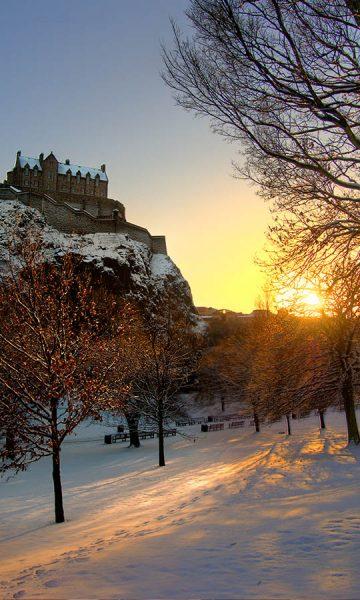Edinburgh Castle at sunset with a snow covered parkland beneath it