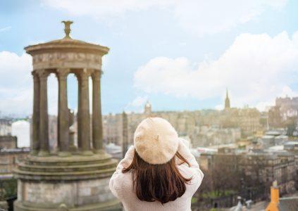 A tourist taking a photo of Edinburgh City from Calton Hill