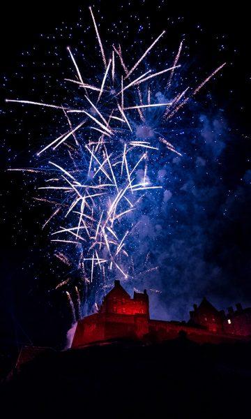 Edinburgh Castle lit up with fireworks over head