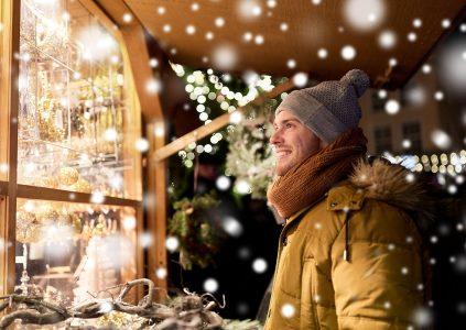 A man looking at Christmas market stall