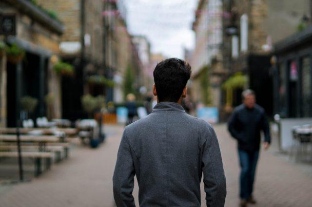 A man walking down Rose Street in Edinburgh