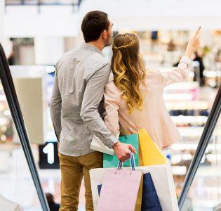 A couple going down an escalator in an indoor shopping centre