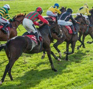 Horses and their jockeys racing on a track
