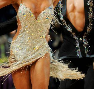Ballroom dancers dancing an energetic dance in sparkling costumes
