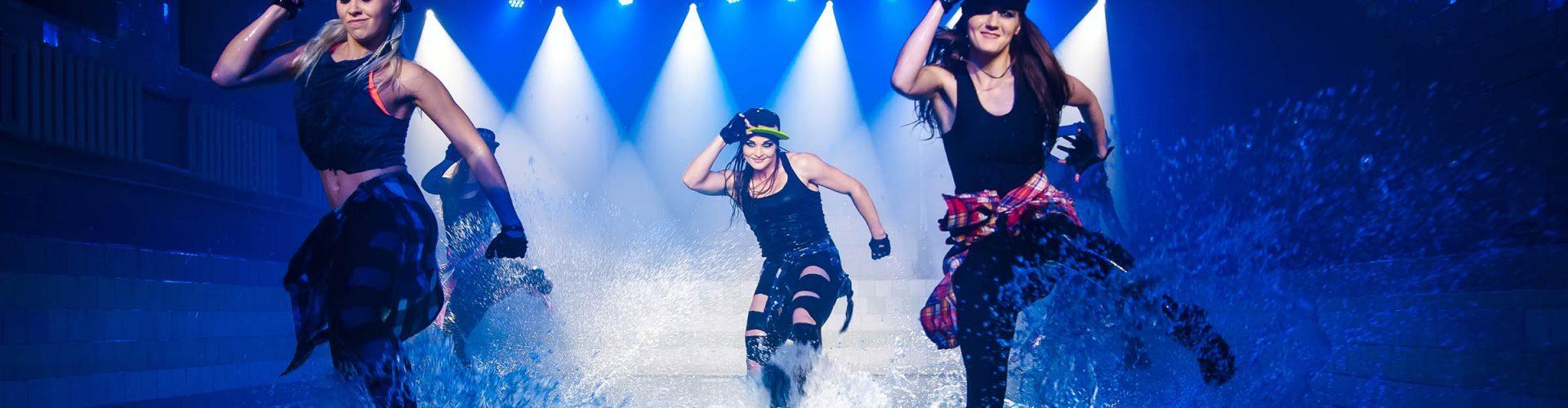 Dancers performing on stage dancing in water