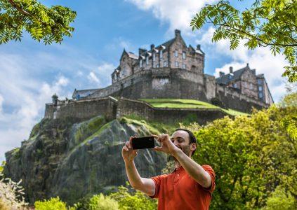 A tourist taking a selfie with Edinburgh Castle behind him