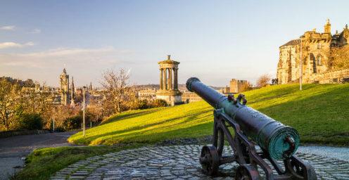 Cannon and historic monuments atop Calton Hill in Edinburgh