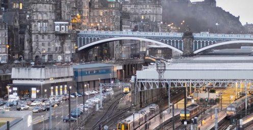 Trains at Edinburgh's Waverley Train Station with North Bridge in the background.