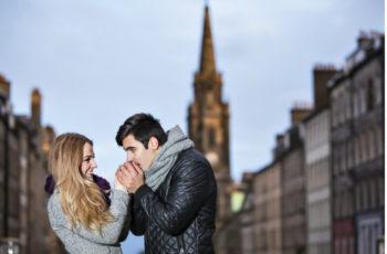 Couple enjoying winter breaks in Edinburgh in front of Scott Monument