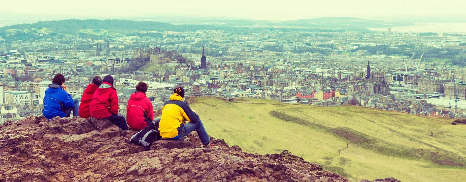 Walkers resting on the rocks overlooking Edinburgh