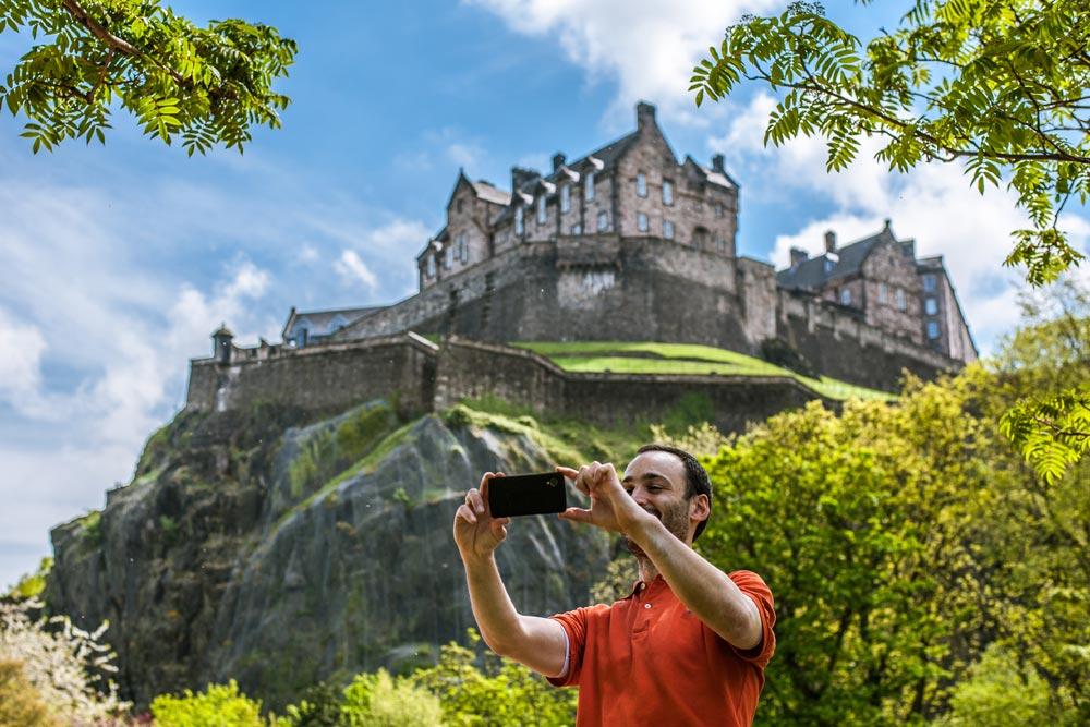 Man taking a selfie beneath Edinburgh Castle