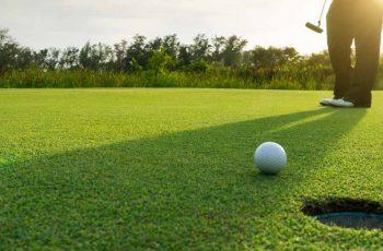 Golfer putting ball on golf course
