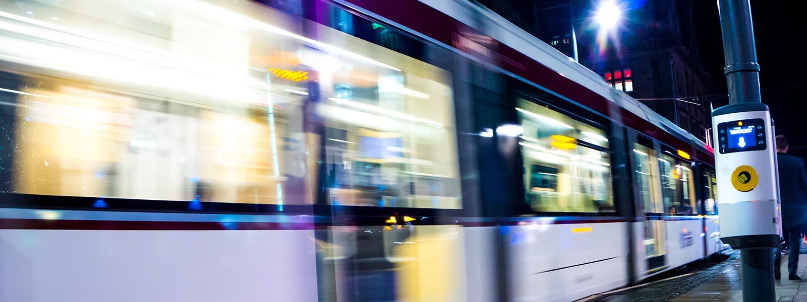 An Edinburgh Tram zooms past the camera